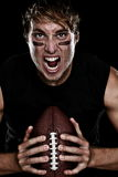 American football player. Screaming aggressive holding american football on black background. Strong fit Caucasian fitness man stock photos