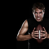 American football player. Staring aggressive holding american football on black background. Strong fit Caucasian fitness man with black copy space Royalty Free Stock Image
