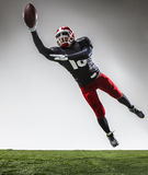 The american football player in action. On green grass and gray background Royalty Free Stock Photo