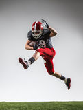 The american football player in action. On green grass and gray background Stock Photo