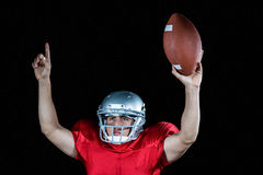 American football player with arms raised holding ball Stock Images