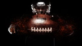 American football player, athlete in helmet with ball on black background. Sport wallpaper with copyspace. American Football player on stadium with smoke and stock photo