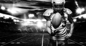 American football player, athlete in helmet with ball on stadium. Black and white photo. Sport wallpaper with copyspace. American Football player on stadium royalty free stock photography