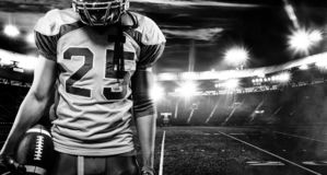 American football player, athlete in helmet with ball on stadium. Black and white photo. Sport wallpaper with copyspace. stock photos