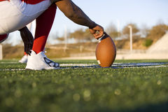 American football player attempting to kick field goal, teammate holding ball vertically against pitch (surface level) Stock Photo