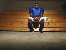 American Football Player With Ball On Bench Royalty Free Stock Photos