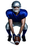 American football player with ball crouching Royalty Free Stock Image