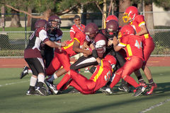 American Football Player Being Tackled During a Ga. A football player on the Gunderson Grizzlies is tackled during a game against the Mountain View Marauders in Stock Images