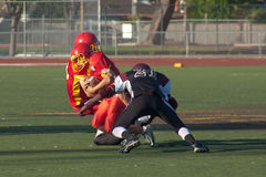 American Football Player Being Tackled During a Ga. A football player on the Mountain View Marauders is tackled during a game against the Gunderson Grizzlies in Stock Image