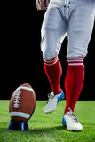 American football player being about to kick football Stock Photos
