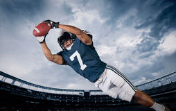 American Football Player Catching a touchdown Pass. In a large stadium. View from below royalty free stock photo