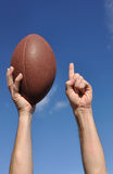 American Football Player Celebrates a Touchdown. Holding a American Football and Giving a Number One Sign Stock Image