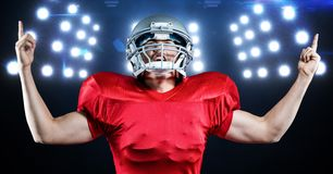 American football player celebrating against floodlights in background Stock Photos