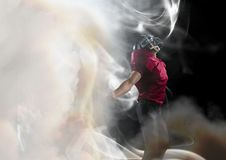 American football player cheering in smoke. Digital composite of American football player cheering in smoke Royalty Free Stock Photography