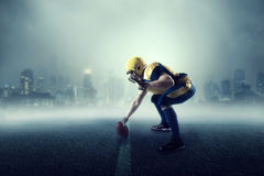 American football player, cityscape on background. American football player with ball, cityscape on background. National league royalty free stock photo