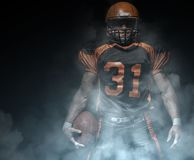 American football player on a dark background in smoke in black and orange equipment