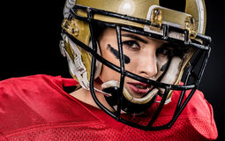 American football player in helmet. Close-up portrait of female american football player in sportswear and helmet on black Royalty Free Stock Photography
