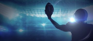 Composite image of american football player in helmet holding rugby ball. American football player in helmet holding rugby ball against american football arena stock photos
