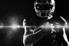 American football player in helmet holding rugby ball. Against black background stock image