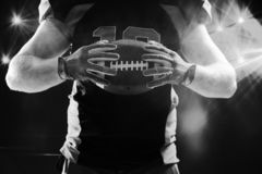 American football player in helmet holding rugby ball. Mid section of American football player in helmet holding rugby ball stock images