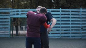 Man helping his mate to put on football jersey. American football player helping his mate to put on jersey before game on field stock footage