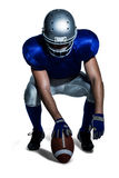 American football player holding ball while crouching Stock Photo