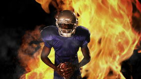 American football player holding ball. On flaming background stock video footage