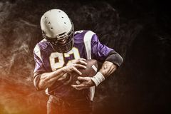 American football player holding ball in his hands in smoke. Black background, copy space. The concept of American