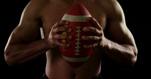 American football player holding ball 4k. American football player holding ball against black background 4k stock video