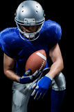 American football player holding ball while kneeling Stock Photo