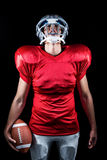 American football player holding ball while looking up Stock Photo
