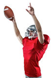 American football player holding ball while pointing up. Against white background Stock Photos