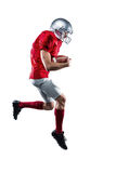 American football player holding ball while running Stock Photos