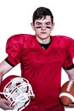 American football player holding helmet and a ball Royalty Free Stock Photography