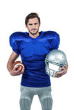 American football player holding helmet and ball Royalty Free Stock Image