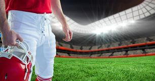 American football player holding a helmet in stadium