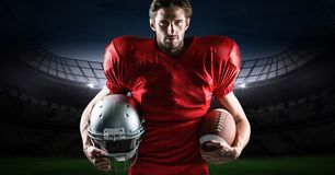 American football player holding rugby ball and helmet against stadium in background Stock Photo