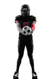 American football player holding soccer ball  silhouette Royalty Free Stock Photography