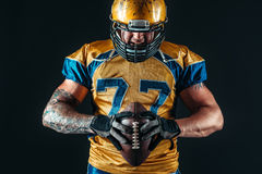 American football player holds ball in hands Royalty Free Stock Photo