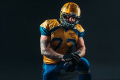 American football player holds ball in hands Royalty Free Stock Images