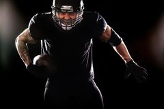 American football sportsman player isolated on black background Royalty Free Stock Image