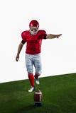American football player kicking football Stock Image