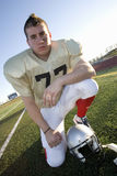 American football player kneeling beside protective helmet on pitch, front view, portrait (tilt) Stock Image