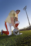 American football player kneeling beside protective helmet on pitch, side view, portrait (surface level, tilt) Stock Images