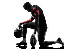 American football player kneeling silhouette. One american football player kneeling in silhouette shadow on white background royalty free stock image