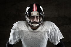 American football player looking at camera on concrete background Royalty Free Stock Photography