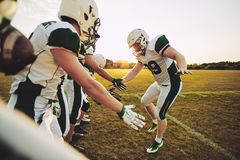 American football player low fiving his teammates after a game. American football player giving his teammates low fives on a sportsfield field after a winning royalty free stock image
