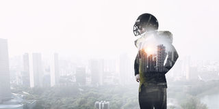 American football player    . Mixed media. Exposure image of confident American football player against modern city background Stock Photography