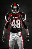 American football player. Portrait of american football player looking at camera on dark background Stock Photos