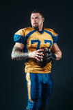 American football player poses with ball in hands Stock Image